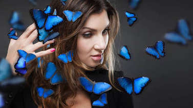 Beauty Fashion Model Girl surrounded by swarms of butterflies. Grey background