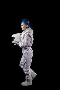 Astronaut on a black background, a young woman with face art in the space suit. Goes to the left