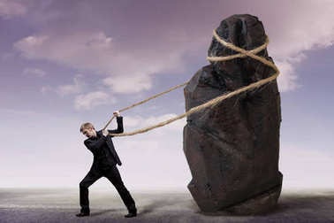 Businessman and a heavy burden, work concept. Young man in a suit is trying to move a huge stone