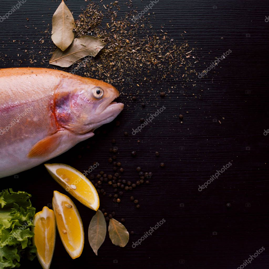 Fresh trout and ingredients to prepare fish dishes on black table. copy space