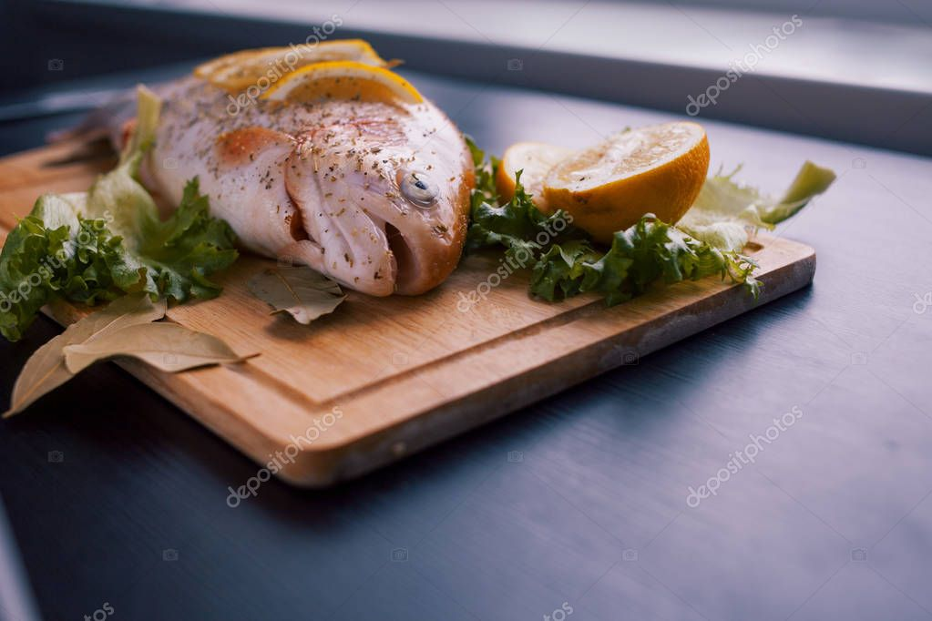 Fresh trout and ingredients to prepare fish dishes on black table
