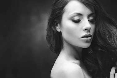 Black and white portrait of an attractive young woman. Beautiful model with curly hairstyle