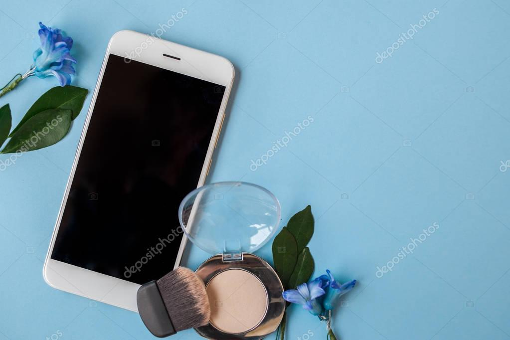 Set cosmetics and Smartphone , women's style, blue background