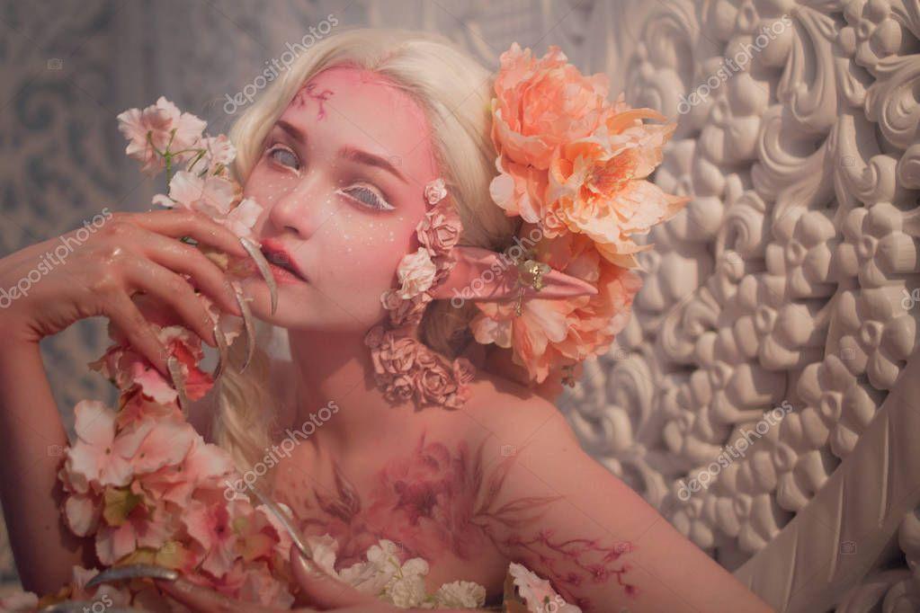 lovely she-elf among flowers. Creative make-up and bodyart