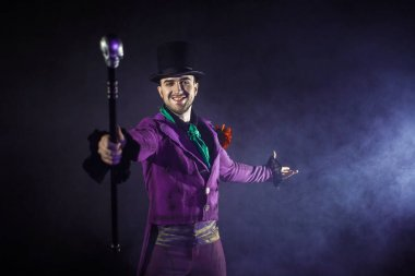 Showman. Young male entertainer, presenter or actor on stage. The guy in the purple camisole and the cylinder.