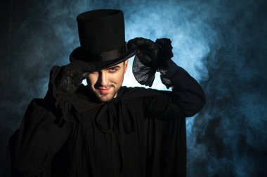 Man in a black top hat and cloak. Demonic image. Magician illusionist