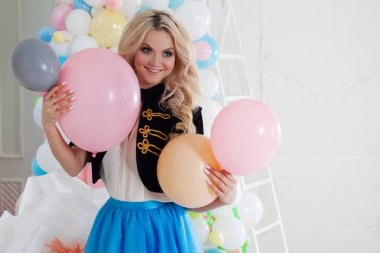 Beautiful young blonde with balloons. Colorful balls.