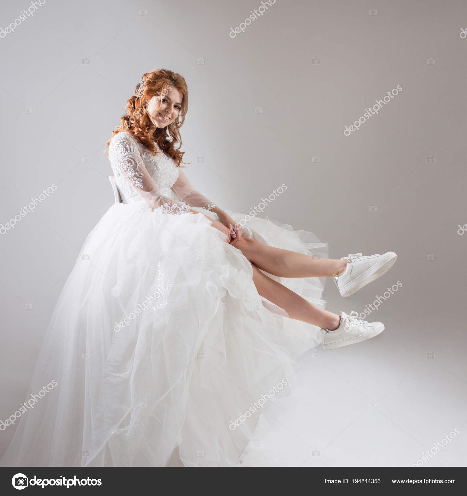Charming girl in magnificent wedding dress and white