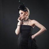 Fotografie Porträt einer eleganten gotischen blonde Frau. Mädchen im Kranz der schwarzen Blüten und schwarzen Mantel