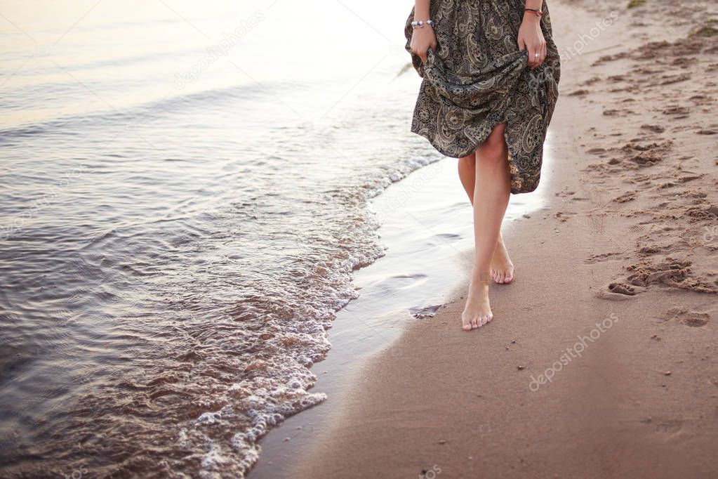 Young woman walking barefoot on surf line, Legs and skirt close up