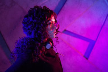 Portrait of young curly pensive sensual woman in big headphones, removed from the head, and shades, on neon background.
