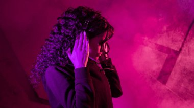 Young beautiful curly woman in big headphones listens to music, sings along, dances against the background of a wall.