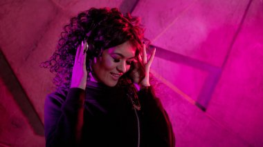 Young beautiful curly woman in big headphones smiles, listens to music, sings along, dances, jumps, closing her eyes.