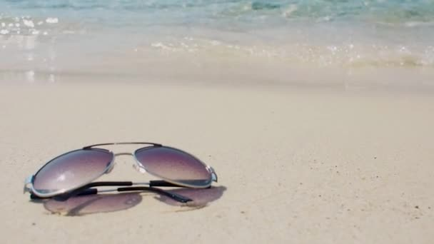 Sunglasses on white sand on blue wave background. Vacation by the warm sea