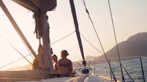 A lányok a jacht fedélzetén ülnek és élvezik a naplementét. Hajókirándulás egy vitorlás jachton,