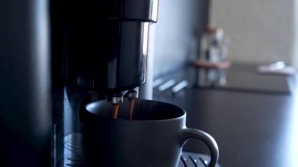 Making coffee using an automatic coffee machine, hot strong coffee is poured into a gray mug,