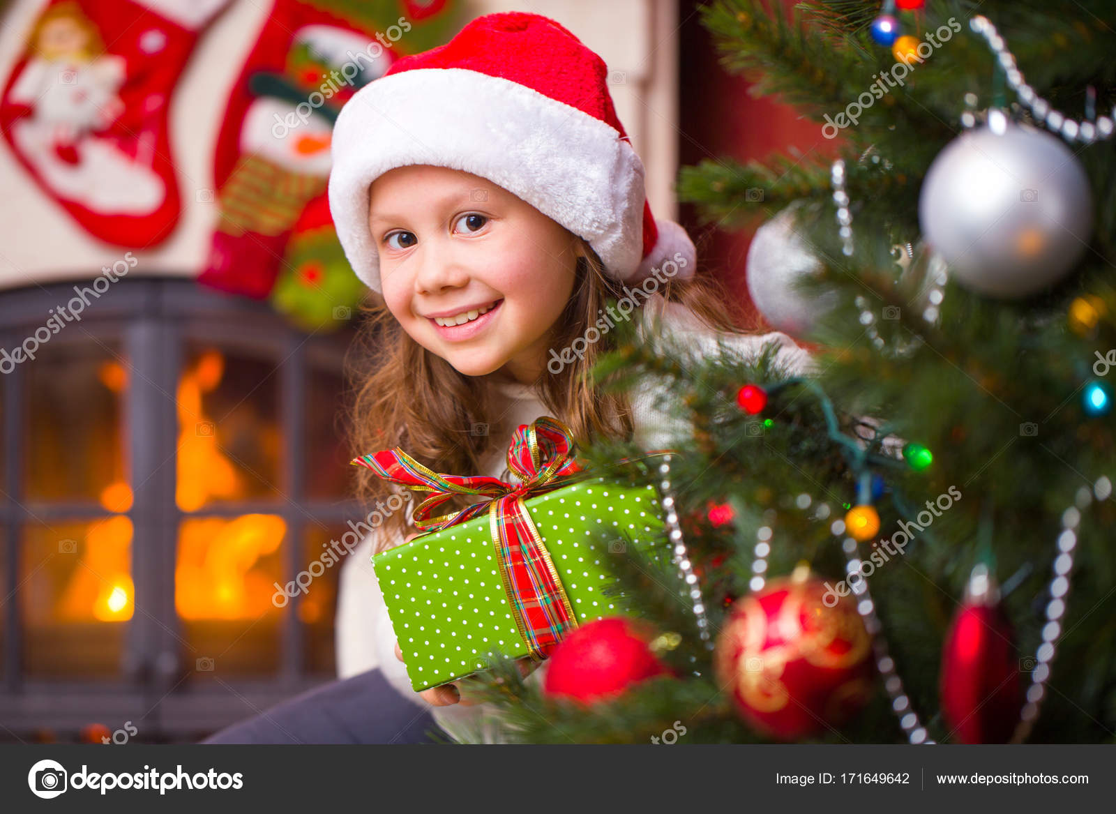 3a3a5e0680c4d Little girl in Santa hat holding a present under the Christmas tree — Photo  by yanlev
