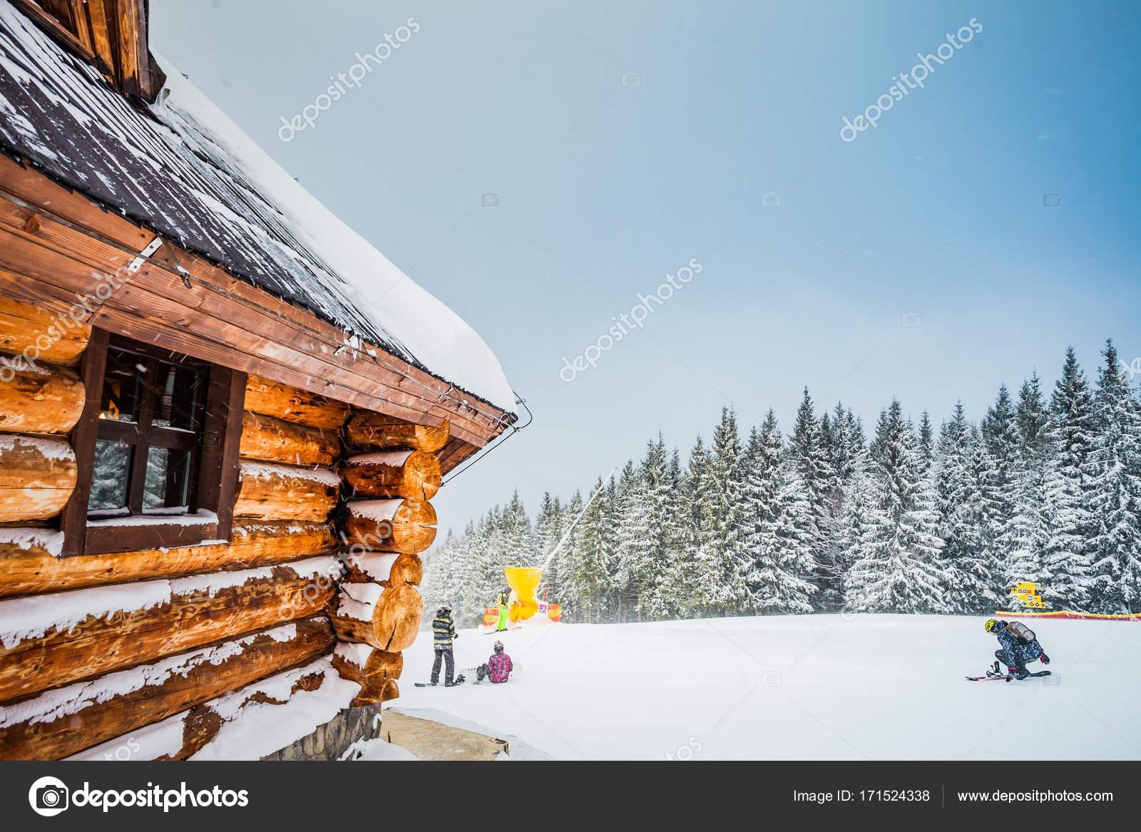 0f42278ee5 Téli pihenés nyaralás faház a hegyekben hóval. Fenyő fa erdő és a kék ég, a  háttérben. Aktív emberek ski, snowboad. Sport, kikapcsolódás.