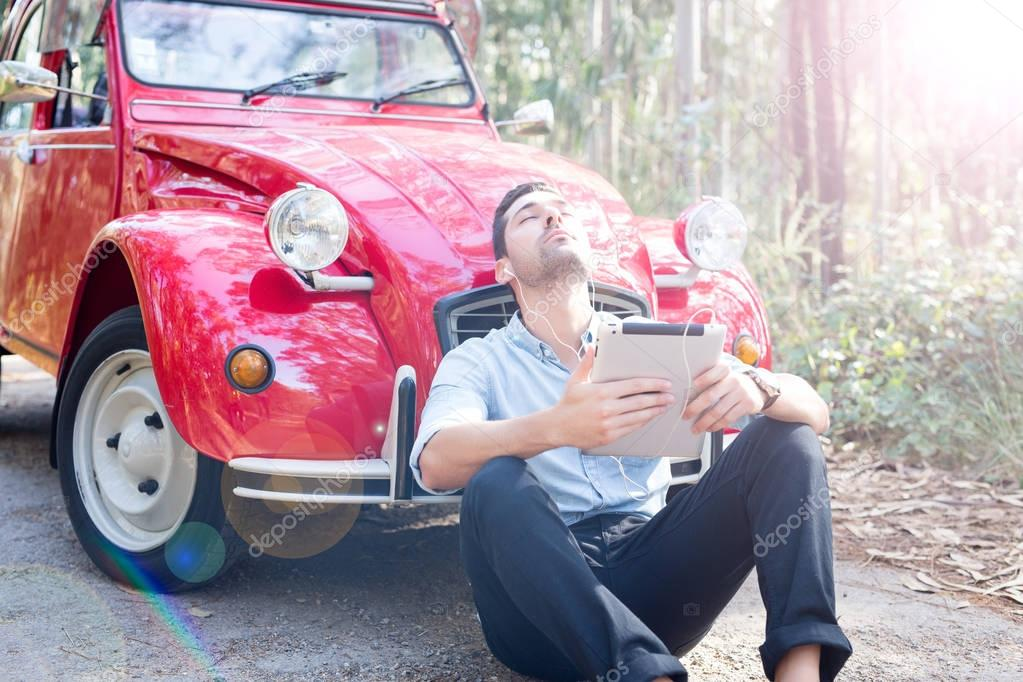 Young man resting at car