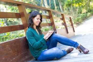 Woman with a tablet computer at the park