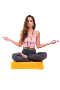 Sporty young woman doing yoga practice on white studio background, concept of healthy life and natural balance between body and mental development