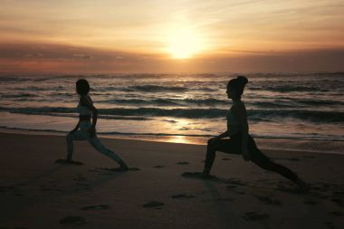 Sporty young women doing yoga practice at the beach - concept of healthy life and natural balance between body and mental development