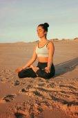 Fotografie Sportovní mladá žena, která dělá cvičení jógy na pláži, koncept zdravého života a přirozenou rovnováhu mezi tělem a duševní vývoj