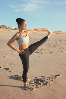 Sporty young woman doing yoga practice at beach, concept of healthy life and natural balance between body and mental development