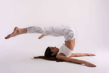 Sporty young woman doing yoga practice on white studio background