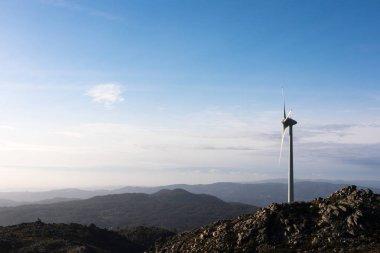 Wind energy turbine, in a landscape over a beautiful blue sky