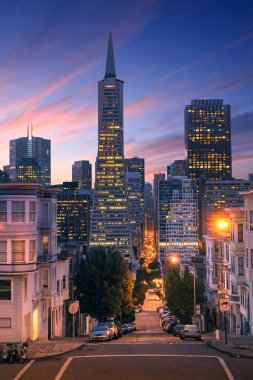 San Francisco downtown at sunrise - night. Famous typical buildings in front. California theme.
