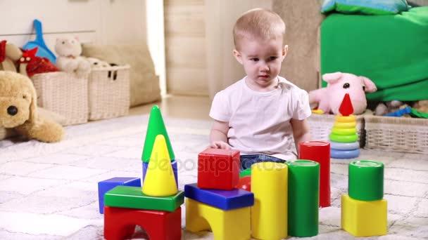 malý chlapec hraje s plastovou bloky