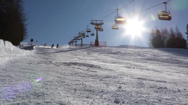 Lyžaři jezdí lyžovat na sjezdovce na jasném slunci. Livigno, Itálie