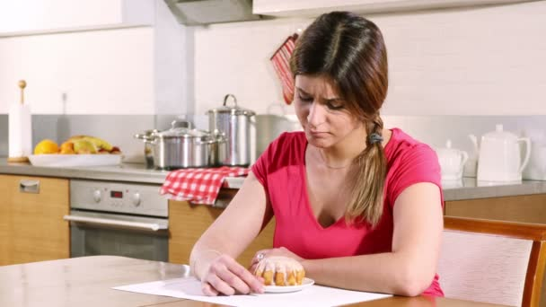Young woman sitting at a table in the kitchen is in doubt whether she should eat a cake