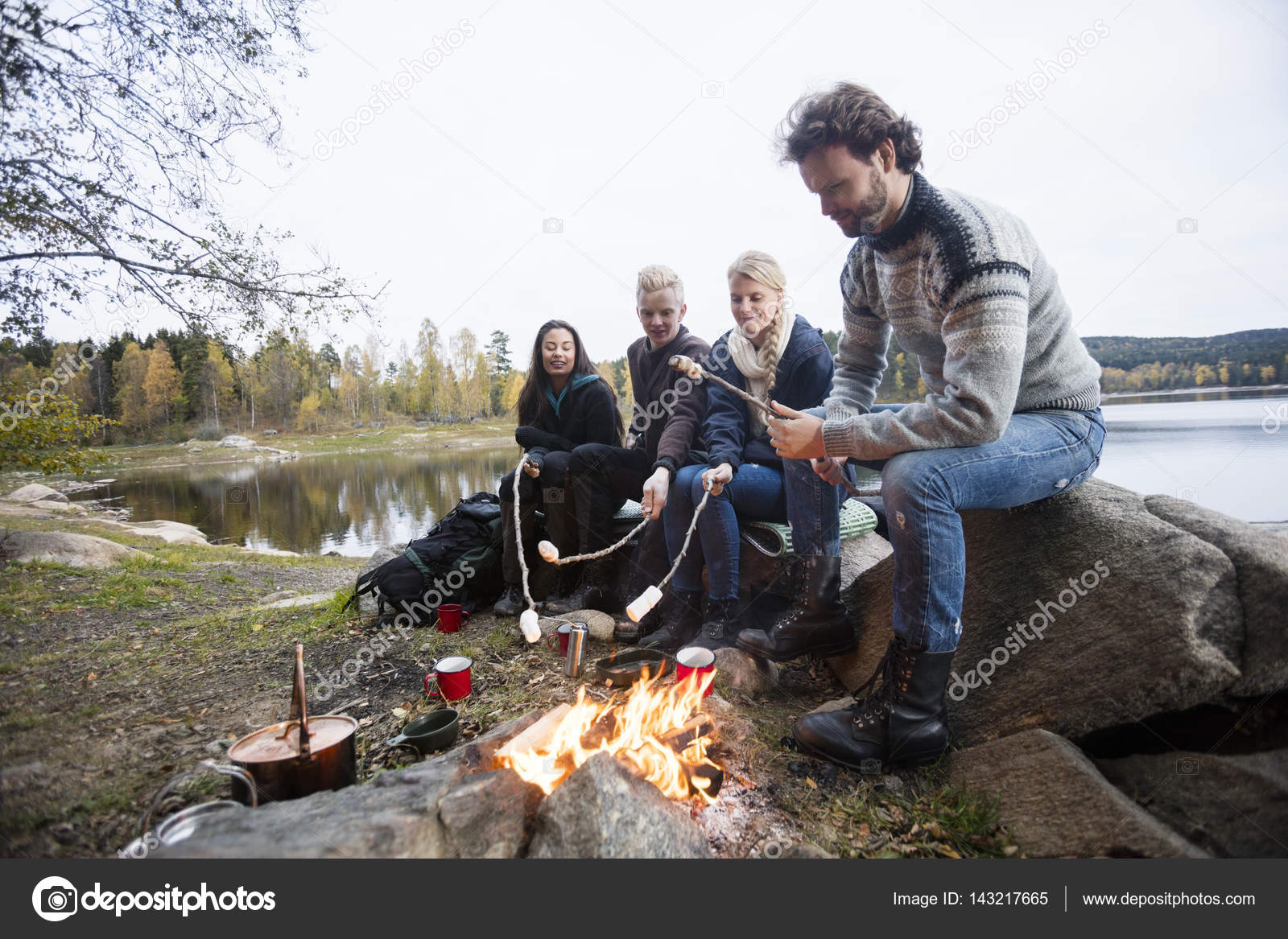 Friends Roasting Marshmallows Over Campfire At Lakeshore Stock Photo