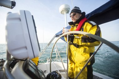 Man Holding Coffee Cup While Standing At Helm Of Sail Boat