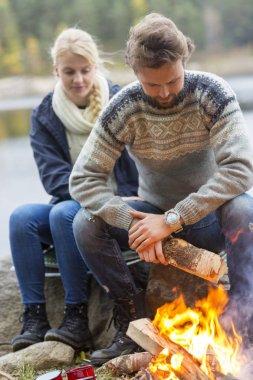 Couple Preparing Bonfire During Lakeside Camping