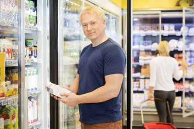 Portrait Of Customer Holding Juice Packet In Grocery Store