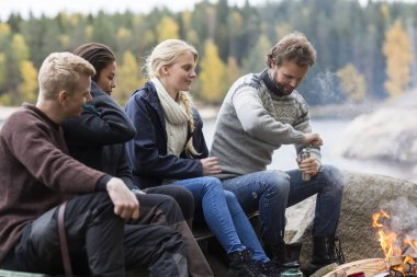 Friends Looking At Man Grinding Coffee At Campsite