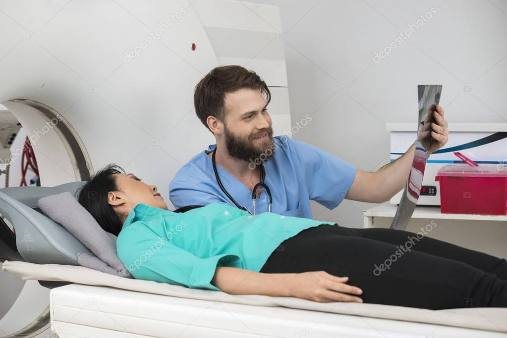 Male Radiologist Showing X-ray Report To Female Patient