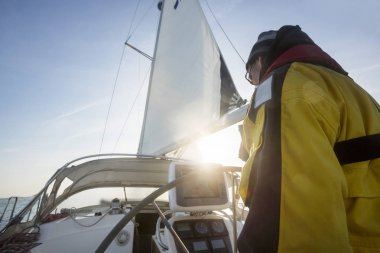 Mature Man At Helm Sailing Yacht