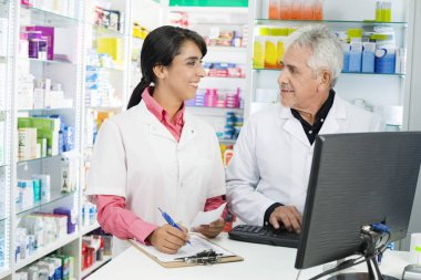 Chemist Writing On Clipboard While Looking At Colleague Using Co
