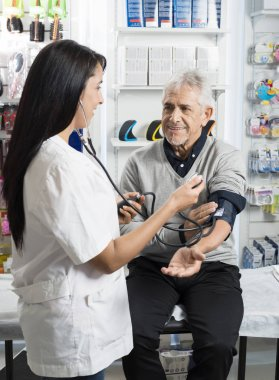 Female Chemist Checking Blood Pressure Of Senior Patient