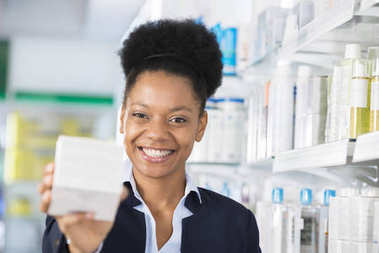 Happy Businesswoman Showing Medicine Box In Pharmacy