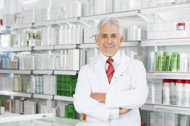 Pharmacist With Arms Crossed Standing In Pharmacy