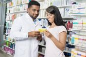 Woman Showing Product To Chemist In Pharmacy