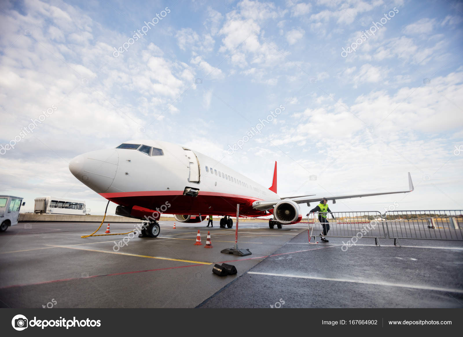 Commercial Airplane On Wet Runway Against Cloudy Sky Stock Photo
