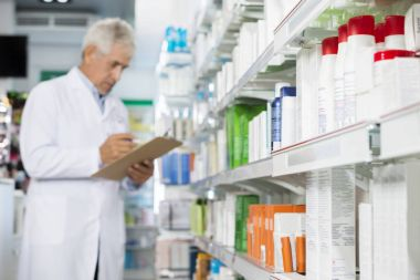 Pharmacist Holding Clipboard While Counting Stock