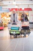 Fotografie Pár šťastný Citi se zavazadly v vozíky na letišti