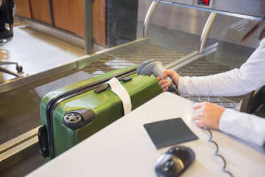 Woman Scanning Tag On Baggage At Airport Check-in